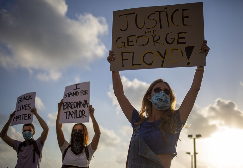 FILE – In this Tuesday, June 2, 2020 file photo protesters hold signs and shout slogans during a protest to decry the killing of George Floyd in front of the U.S. Embassy Branch Office, in Tel Aviv, Israel. (AP Photo/Ariel Schalit, File)