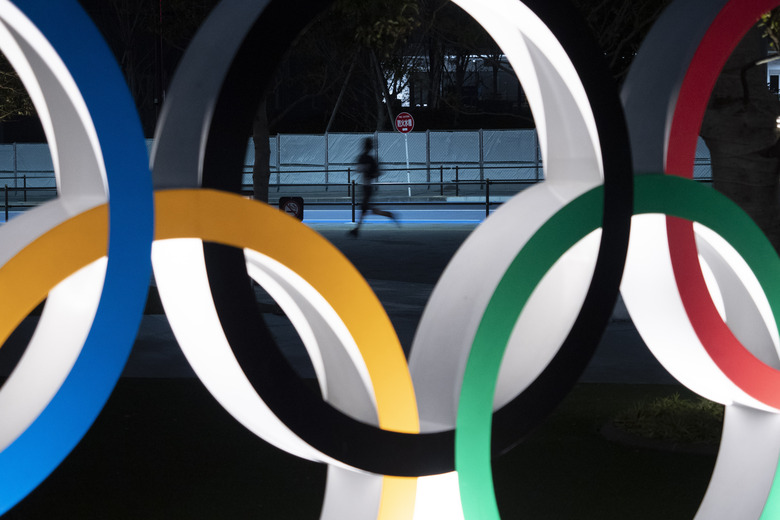 FILE – In this March 30, 2020, file photo, a man jogs past the Olympic rings in Tokyo. Former Olympic minister Toshiaki Endo said at a meeting of the ruling Liberal Democratic Party on Friday, June 5, 2020, that a decision of whether to hold the Games should be made around March, which is a crucial time to finalize participating athletes, NHK said. (AP Photo/Jae C. Hong, File)