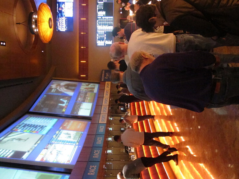 FILE – In this March 21, 2019 file photo, gamblers line up to place bets on the NCAA men's basketball tournament at the Borgata casino in Atlantic City N.J. After being closed since March due to the coronavirus outbreak, the Borgata will reopen to the general public on July 6, 2020 _ four days after much of its competition. Instead, the casino will be doing a test run for an invitation-only audience during those four days. (AP Photo/Wayne Parry, File)