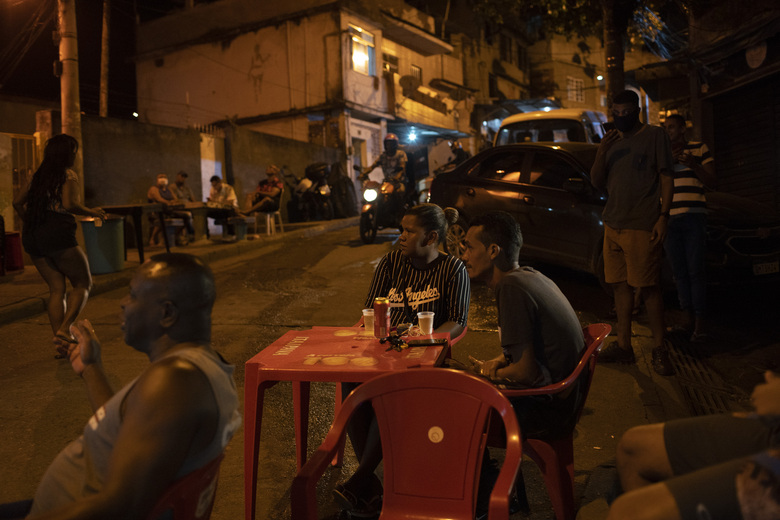 """Residents watch members of """"Tempero de Criola"""" perform in the Turano favela amid the new coronavirus pandemic, in Rio de Janeiro, Brazil, Friday, June 19, 2020. A group of musicians playing Samba offered a small concert to the residents of Turano favela, most of whom remain quarantined to curb the spread of COVID-19. Residents could watch the performance from their windows, balconies or via internet. (AP Photo/Silvia Izquierdo)"""