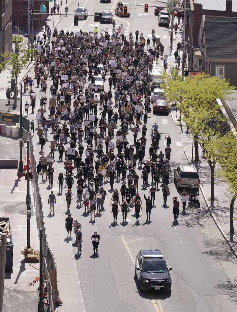 FILE – In this May 31, 2020 file photo, protesters march along a street in Portland, Maine, during a demonstration over the death of George Floyd, who died May 25 after he was pinned at the neck by a Minneapolis police officer. Public outrage over the death of Floyd while in Minneapolis police custody is spilling over into America's smaller and mid-sized cities. (Gregory Rec/Portland Press Herald via AP, File)