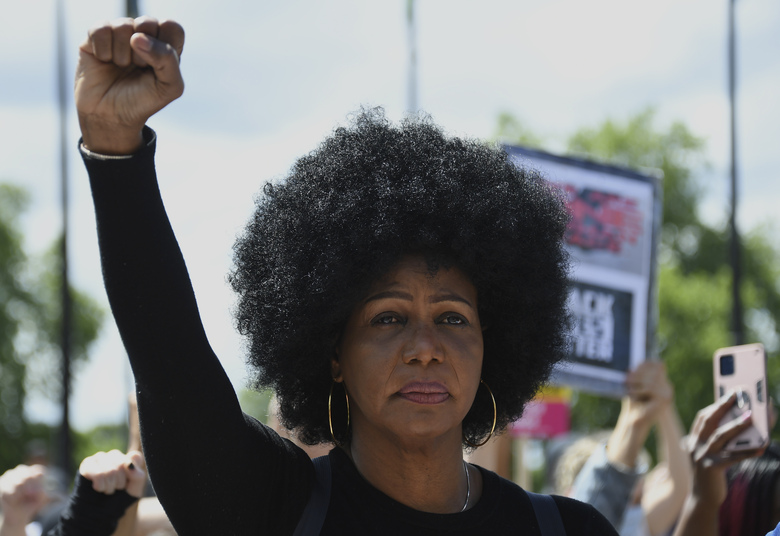 A member of Black Lives Matter movement raises her fist as she kneels during a protest at Hyde Park in London, Saturday, June 13, 2020. British police have imposed strict restrictions on groups planning to protest in London Saturday in a bid to avoid violent clashes between protesters from the Black Lives Matter movement, as well as far-right groups. (AP Photo/Alberto Pezzali)