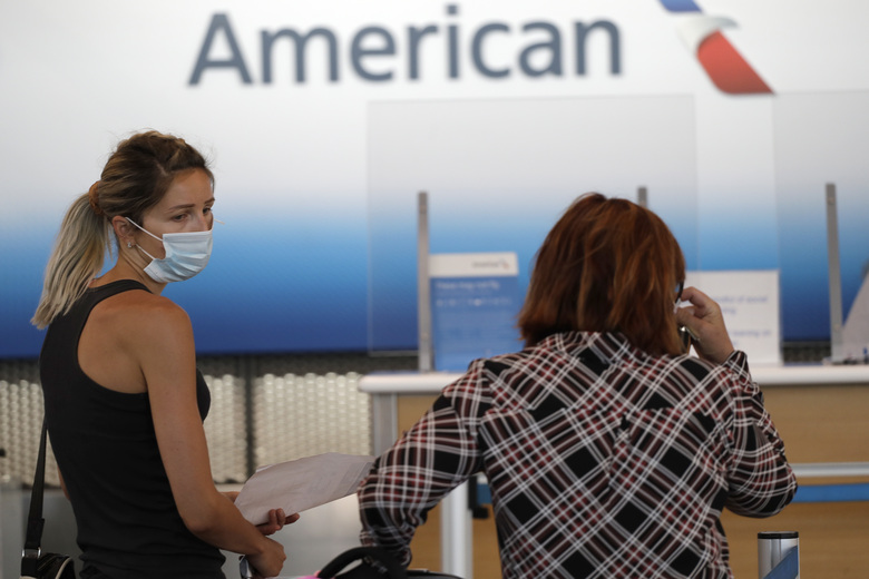 Travelers wear masks as they wait at the American Airlines ticket counter at O'Hare International Airport in Chicago. American Airlines has banned a man who was kicked off a plane for refusing to wear a face covering, among the first such incidents since airlines promised this week to step up enforcement of their mask rules. (AP Photo/Nam Y. Huh)