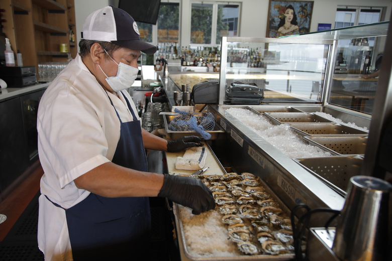 Victor Ek prepares oysters at Mission Rock restaurant on Friday, June 12, 2020, in San Francisco. Today was the first day patio / outdoor dining is allowed in San Francisco restaurants since the COVID-19 pandemic. (AP Photo/Ben Margot)