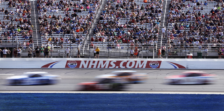 FILE – In this July 16, 2017, file photo, cars steer through Turn 1 as fans watch from nearly half-full stands during the NASCAR Cup Series 301 auto race at New Hampshire Motor Speedway in Loudon, N.H. New Hampshire Motor Speedway will allow fans in the grandstands and suites for the Aug. 2 NASCAR Cup Series race.  Fans will be subject to social distancing requirements and additional health and safety protocols.  (AP Photo/Charles Krupa, File)