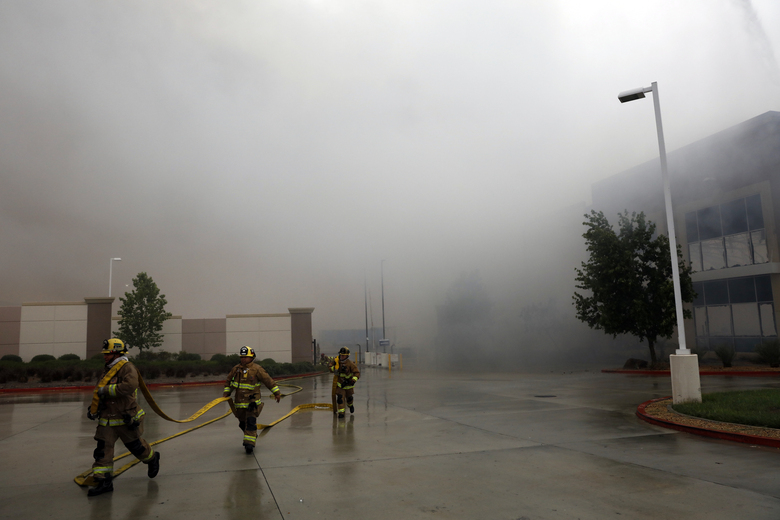 Firefighters carry a water hose as smoke from a burning warehouse fills the air Friday, June 5, 2020, in Redlands, Calif. The fire destroyed the commercial building, about 60 miles east of Los Angeles, but there are no reports of injuries. (AP Photo/Jae C. Hong)