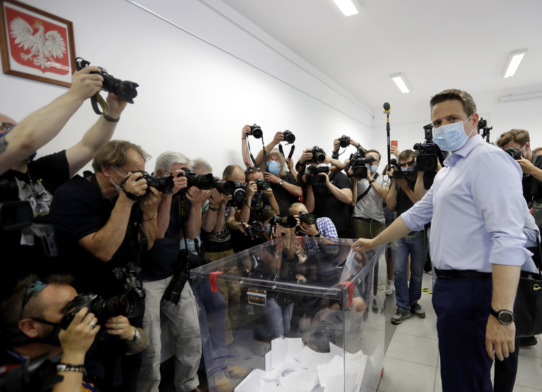 Presidential candidate Rafal Trzaskowski casts his vote during presidential election in Warsaw, Poland, Sunday, June 28, 2020. The election will test the popularity of incumbent President Andrzej Duda who is seeking a second term and of the conservative ruling party that backs him. (AP Photo/Petr David Josek)