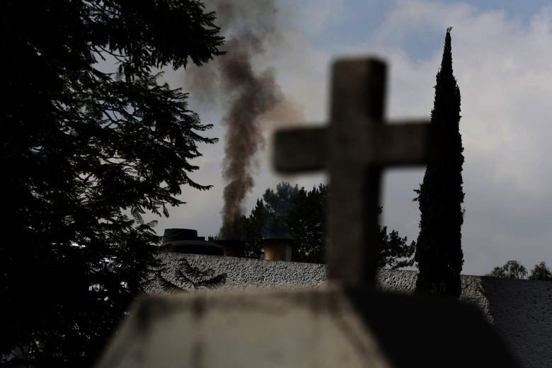 Smoke rises from the crematorium at the Panteón de San Nicolas Tolentino cemetery in the Iztapalapa neighborhood of Mexico City, Tuesday, June 2, 2020. In the first days of the pandemic in March, they cremated 15 bodies per day. By May, that number had risen to between 30 and 35 per day. (AP Photo/Marco Ugarte)