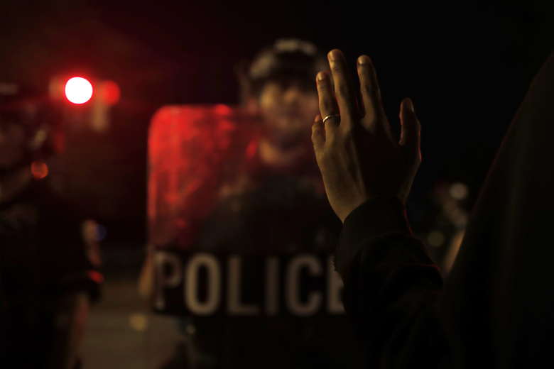 FILE – In this June 23, 2020, file photo a man gestures to Metropolitan Police Department officers standing guard after police closed the area around Lafayette Park near the White House after protesters tried to topple a statue of Andrew Jackson in the park in Washington. (AP Photo/Maya Alleruzzo, File)