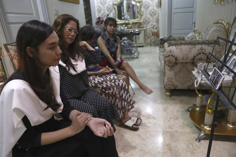 Fiance Tri Novia Septiani, left, and mother Herlina Simbala, second from left, of Dr. Michael Robert Marampe attend an online memorial service to mark the 40th day since Marampe passed away due to COVID-19 in Jakarta, Indonesia, on June 5, 2020. Marampe knew what he wanted to be since he was a kid: a doctor and a pianist. He became both, and his passion for music even led him to Septiani – a woman he never got to marry because he got the coronavirus. Marampe became one of dozens of doctors the coronavirus has claimed so far in Indonesia. (AP Photo/Tatan Syuflana)