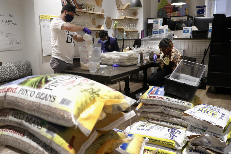 Chad Houser, left, Founder, CEO and Chef at Cafe Momentum fills bags with rice with help from staff members Marquel Gray, center, and Maya Barnes, right, in Dallas, Wednesday, May 13, 2020. Chef Houser opened his downtown Dallas restaurant five years ago to help give teens coming out of juvenile detention stability and a push toward success. (AP Photo/Tony Gutierrez)