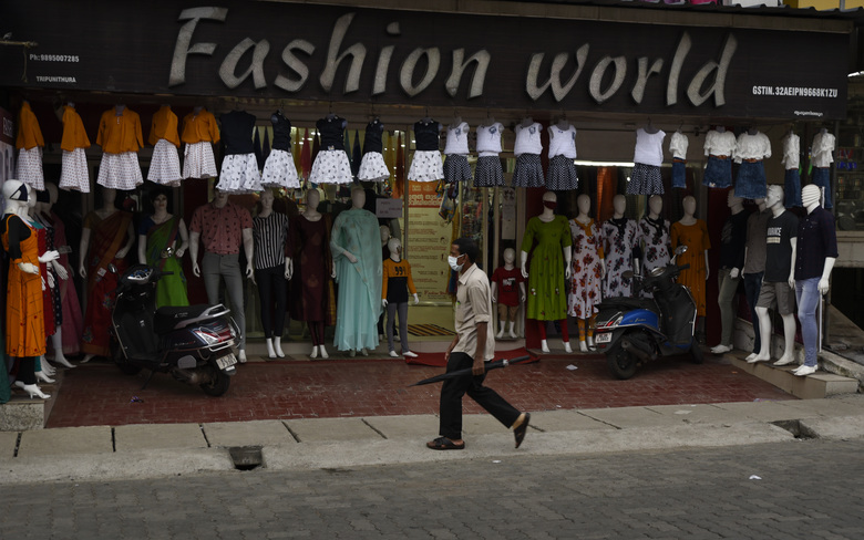 A man wearing a mask as a precaution against the coronavirus walks past a fashion store in Kochi, Kerala state, India, Thursday, June 25, 2020. India is the fourth hardest-hit country by the COVID-19 pandemic in the world after the U.S., Russia and Brazil. (AP Photo/R S Iyer)
