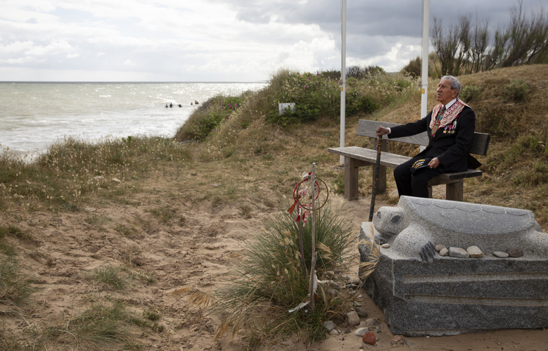 World War II D-Day veteran and Penobscot Elder from Maine, Charles Norman Shay sits on a bench next to his memorial stone at Omaha Beach prior to a ceremony in Saint-Laurent-sur-Mer, Normandy, France, Friday June 5, 2020. Saturday's anniversary of D-Day will be one of the loneliest remembrances ever, as the coronavirus pandemic is keeping almost everyone away, from government leaders to frail veterans who might not get another chance for a final farewell to their unlucky comrades. (AP Photo/Virginia Mayo)
