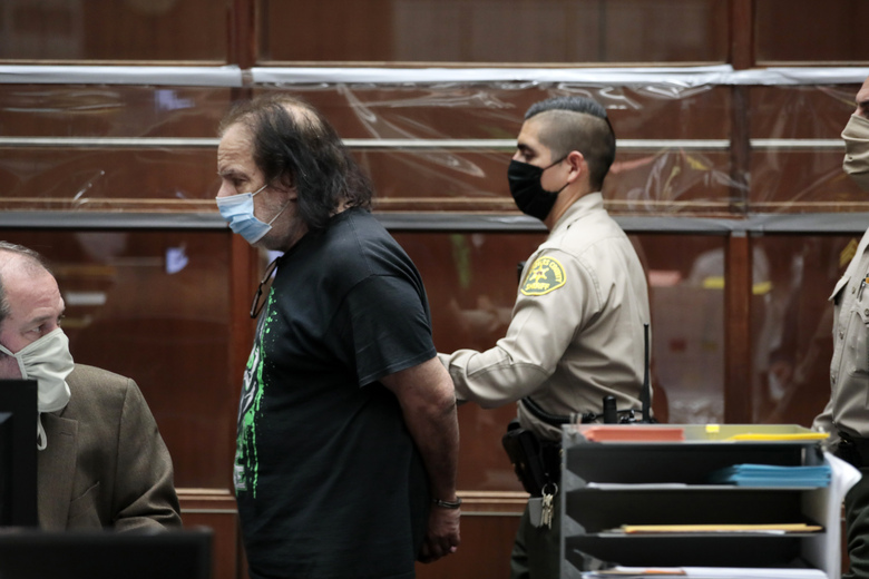 Adult film star Ron Jeremy is lead out of Los Angeles Superior Court after his first appearance in Los Angeles, Tuesday, June 23, 2020. Los Angeles County prosecutors say Jeremy has been charged with raping three women and sexually assaulting a fourth. (Robert Gauthier/Los Angeles Times via AP, Pool)