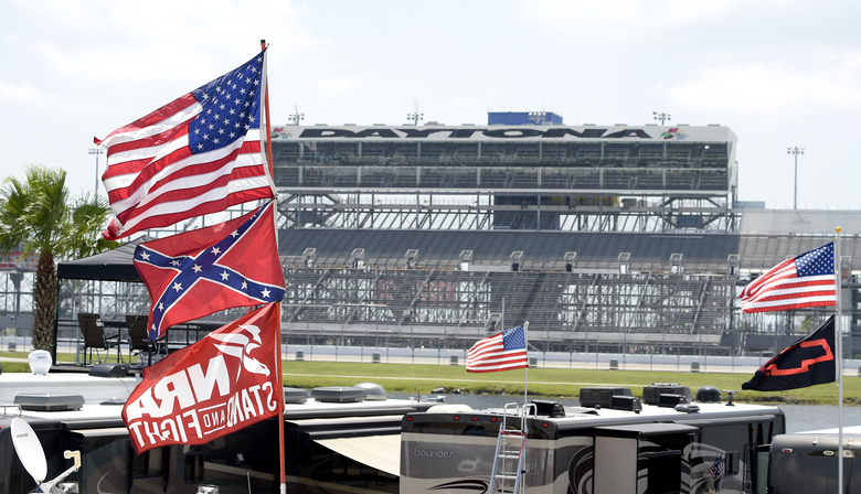 FILE – In this July 4, 2015, file photo, confederate and American flags fly on top of motor homes at Daytona International Speedway in Daytona Beach, Fla. Bubba Wallace, the only African-American driver in the top tier of NASCAR, calls for a ban on the Confederate flag in the sport that is deeply rooted in the South. (AP Photo/Phelan M. Ebenhack, File)