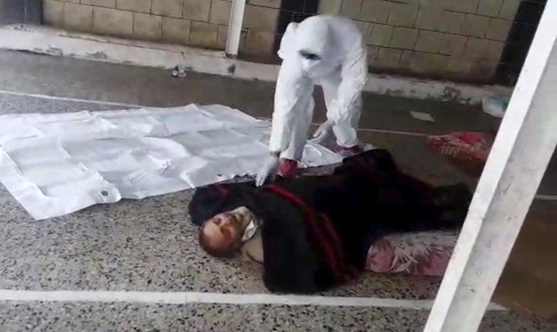 This May 2020 frame grab from video provided by a Yemeni Community activist, shows an activist wearing protective gear collecting the body of a COVID-19 victim, after medics declined to take the body, in the Houthi-controlled city of Ibb, Yemen. An investigation by The Associated Press found that the coronavirus is taking a deadly toll on the war weary population of Yemen. The situation is exacerbated in the Houthi-controlled north where the rebels have suppressed information about the virus, severely punished those who speak out, enforced little mitigation measures, and promoted conspiracies and claims by the Houthi minister of health that scientists are working on developing a cure for covid-19 to present to the world.  (Courtesy of a Yemeni Community Activist via AP)