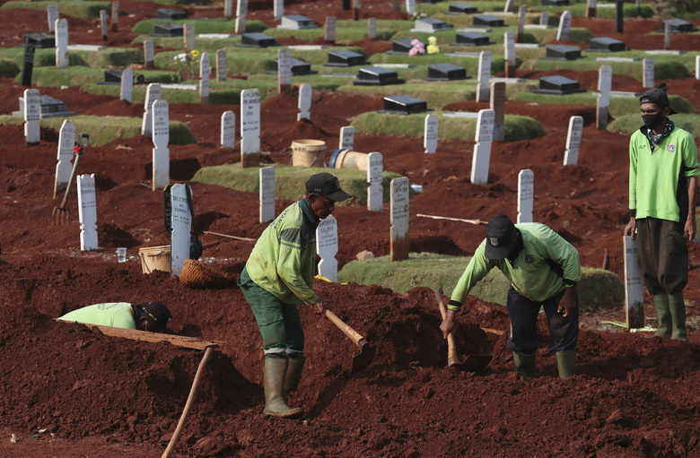 Workers prepare a grave to bury suspected COVID-19 victims at Pondok Ranggon cemetery in Jakarta, Indonesia, Friday, June 12, 2020. (AP Photo/Achmad Ibrahim)