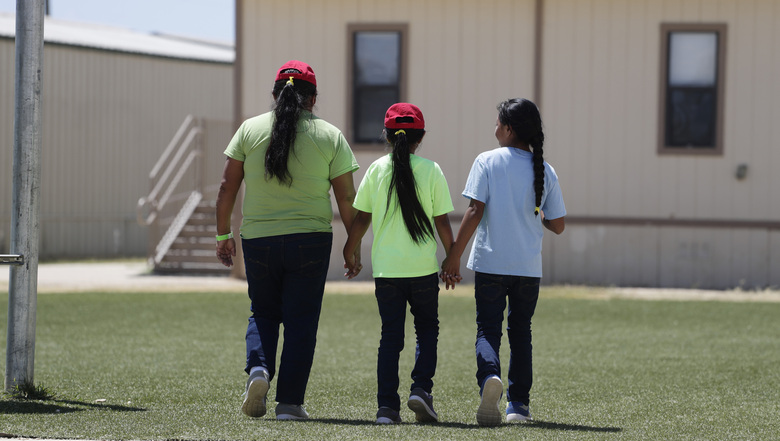 FILE – In this Aug. 23, 2019 file photo, immigrants seeking asylum hold hands as they leave a cafeteria at the ICE South Texas Family Residential Center in Dilley, Texas. The isolation of at least three families at the U.S. Immigration and Customs Enforcement's detention center in Dilley, has raised new fears of the coronavirus spreading through a facility that has long been accused of providing substandard medical care. (AP Photo/Eric Gay, File)