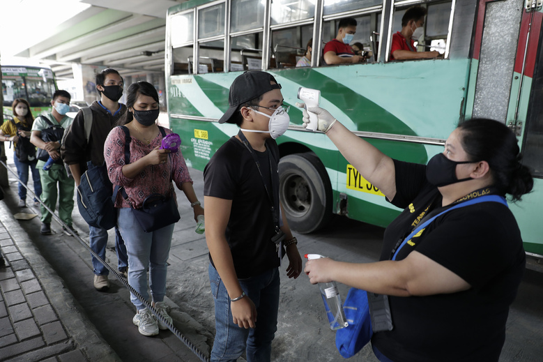People have their temperatures checked before boarding a bus during the first day of a more relaxed lockdown that was placed to prevent the spread of the new coronavirus in Manila, Philippines on Monday, June 1, 2020. Traffic jams and crowds of commuters are back in the Philippine capital, which shifted to a more relaxed quarantine with limited public transport in a high-stakes gamble to slowly reopen the economy while fighting the coronavirus outbreak. (AP Photo/Aaron Favila)