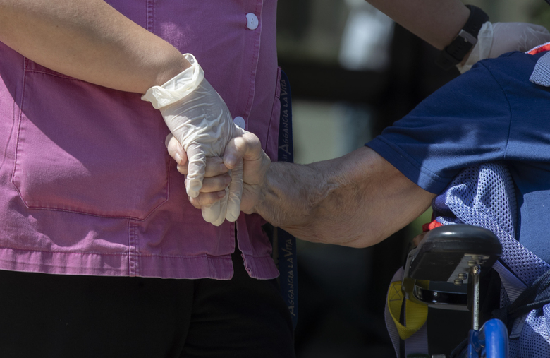Anna Maria Alborghetti sits in a wheelchair as carer Melania Cavalieri holds her hand during a visit by her family at the Martino Zanchi Foundation nursing home in Alzano Lombardo, Italy, Friday, May 29, 2020. (AP Photo/Luca Bruno)