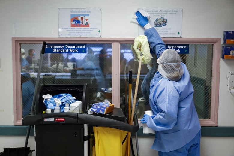 A hospital employee cleans surfaces in the emergency department at NYC Health + Hospitals Metropolitan, Wednesday, May 27, 2020, in New York. At hospitals around the country, nurses, doctors and other health care workers are reckoning with the psychological toll of the virus fight, coupled with fears that the disease could flare anew later this year. (AP Photo/John Minchillo)