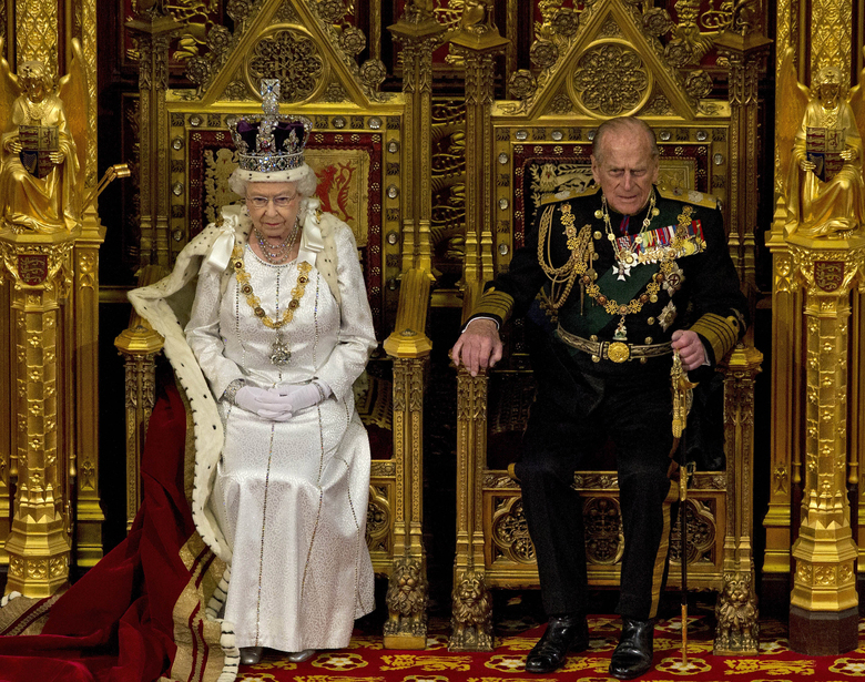 FILE – In this Wednesday, May 9, 2012 file photo, Britain's Queen Elizabeth II sits next to Prince Philip in the House of Lords as she waits to read the Queen's Speech to lawmakers in London. (AP Photo/Alastair Grant, File)