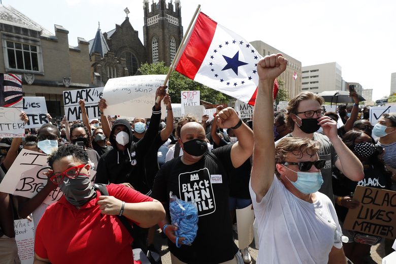 """In this June 6, 2020 photograph, a """"Stennis Flag"""" is waved by protesters gathered at a rally and march in downtown Jackson, Miss., in response to police brutality nationwide including Mississippi. The flag is often suggested as a possible replacement to the current flag that has in the canton portion of the flag the design of the Civil War-era Confederate battle flag. (AP Photo/Rogelio V. Solis)"""