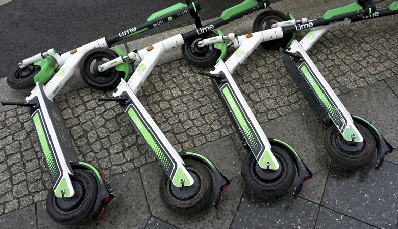 FILE – In this Friday, Sept. 13, 2019 file photo, electric rental scooters lie on a sidewalk in Berlin, Germany. Britain is giving the green light for trials of electric scooter rental programs, as authorities look for ways to help people get moving while maintaining distance and easing pressure on public transit. The transport department on Tuesday, June 30, 2020 unveiled new regulations that take effect on the weekend and pave the way for e-scooter rentals in Britain. (AP Photo/Michael Sohn, file)