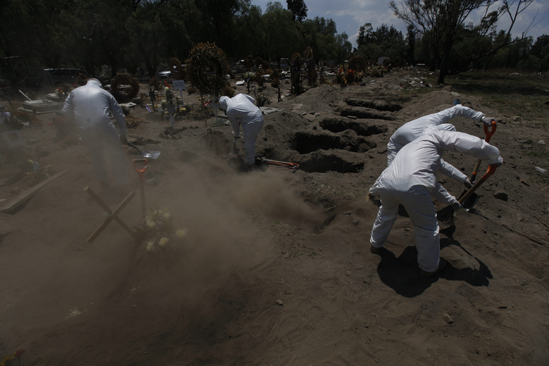 Cemetery workers in a protective gear shovel dirt over the gravesite of a COVID-19 victim at the Panteón de San Lorenzo Tezonco Iztapalapa cemetery, in a section for victims of the new coronavirus, in the Iztapalapa neighborhood of Mexico City, Tuesday, June 2, 2020. Mexico is passing through the pandemic's most critical moment with a dramatically increasing number of confirmed and suspected infections. (AP Photo/Marco Ugarte)