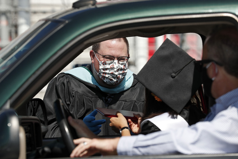 Principal Vance Fishback presents a diploma to a graduate of the class of 2020 from Cabarrus Early College of Technology at the Charlotte Motor Speedway during a graduation event in Concord, N.C., Friday, June 12, 2020. Due to the coronavirus pandemic Cabarrus County schools participated in a first-of-its-kind commencement ceremony for students and family. (AP Photo/Gerry Broome)