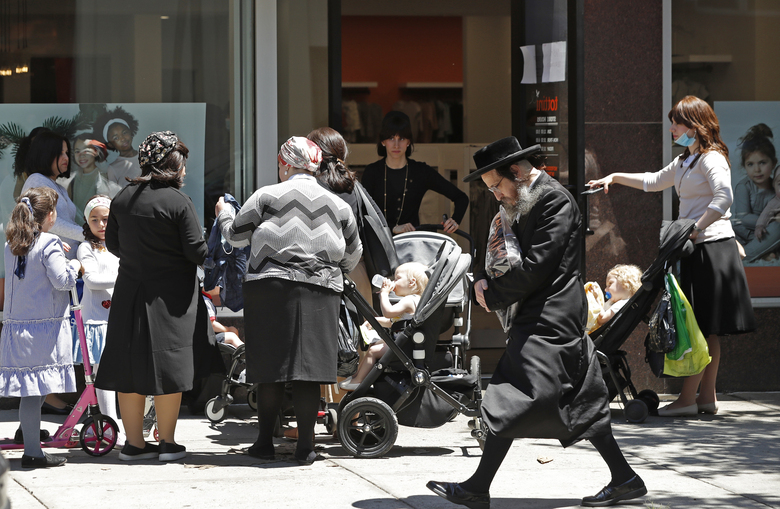 A man walks past a group of women waiting in line to enter a women's clothing shop, Monday, June 8, 2020, in the Borough Park neighborhood of the Brooklyn borough of New York as retail stores opened their doors as part of NewYork state's phase one reopening plan. (AP Photo/Kathy Willens)
