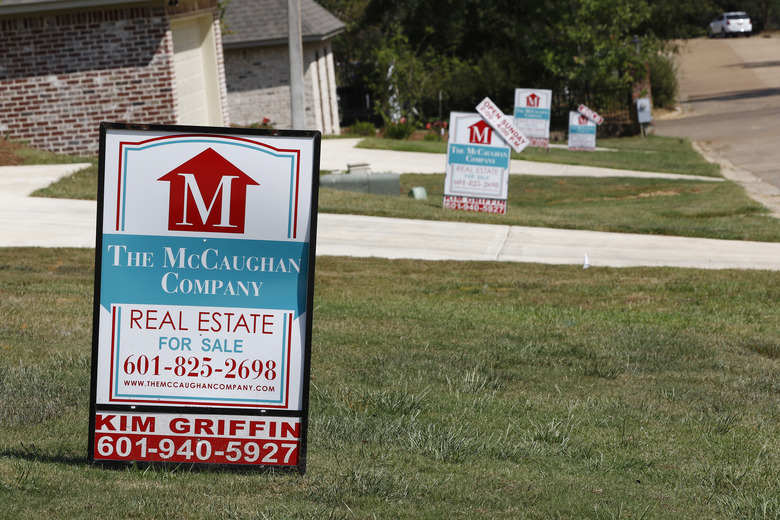 FILE – In this Sept. 25, 2019 file photo, a realty company's signs rest on several lawns in front of newly constructed houses in Brandon, Miss..  Long-term U.S. mortgage rates fell, Thursday, June 18, 2020,  as the benchmark 30-year home loan reached a new all-time low. Mortgage buyer Freddie Mac reports that the average rate on the key 30-year loan declined to 3.13% from 3.21% last week.  (AP Photo/Rogelio V. Solis, File)