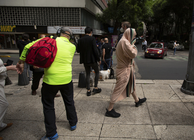 A man, wearing a robe, joins other residents on a pedestrian walkway on Reforma Avenue after they were evacuated from their buildings due to an earthquake, in Mexico City, Tuesday, June 23, 2020. The earthquake centered near the resort of Huatulco in southern Mexico swayed buildings Tuesday in Mexico City and sent thousands into the streets. (AP Photo/Fernando Llano)