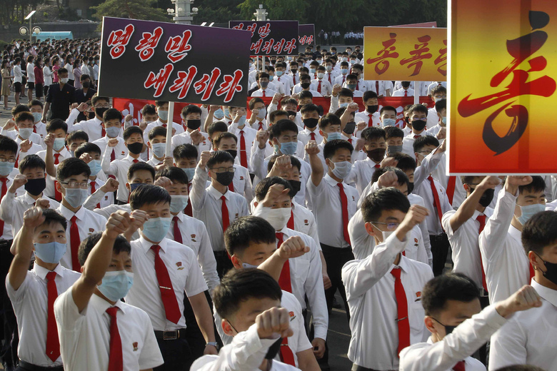 """North Korean youth and students march from the Pyongyang Youth Park Open-air Theatre to Kim Il Sung Square during a protest demonstration to denounce South Korean authorities policy against North Korea and defectors from the north, in Pyongyang, North Korea Monday, June 8, 2020. The signs read """" Give us an order (to punish South Korea)."""" (AP Photo/Jon Chol Jin)"""