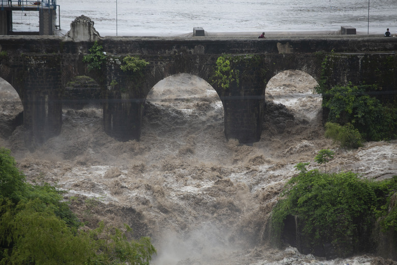 The swollen Los Esclavos River flows violently under a bridge during tropical storm Amanda in Cuilapa, eastern Guatemala, Sunday, May 31, 2020. The first tropical storm of the Eastern Pacific season drenched parts of Central America on Sunday and officials in El Salvador said at least seven people had died in the flooding. (AP Photo/Moises Castillo)