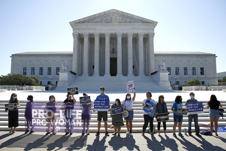 Anti-abortion protesters wait outside the Supreme Court for a decision Monday