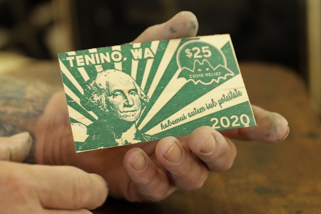 Loren Ackerman holds a piece of wooden money he printed on an 1890s-era press in Tenino, Wash. In an effort to help residents and local merchants alike get through the economic fallout of the coronavirus pandemic, the small town has issued wooden currency for residents to spend at local businesses. Decades earlier, it created a similar program during the Great Depression. (AP Photo/Ted S. Warren)