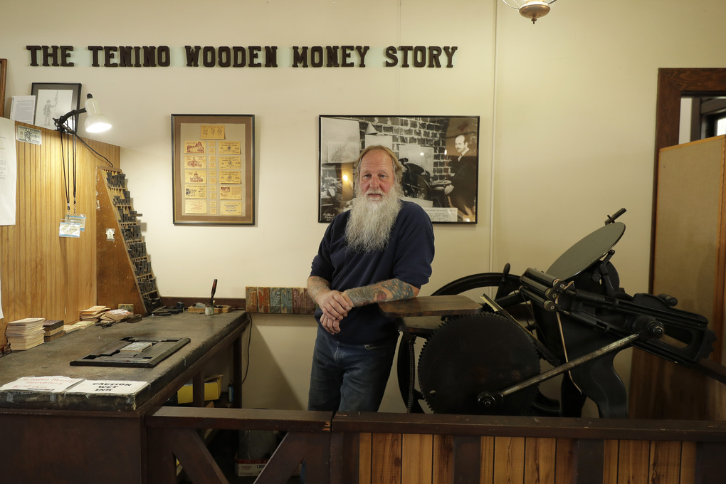 Loren Ackerman leans on an 1890s-era press he uses to print wooden money in Tenino, Thurston County, Wash. In an effort to help residents and local merchants alike get through the economic fallout of the coronavirus pandemic, the small town has issued wooden currency for residents to spend at local businesses, decades after it created a similar program during the Great Depression. (AP Photo/Ted S. Warren)