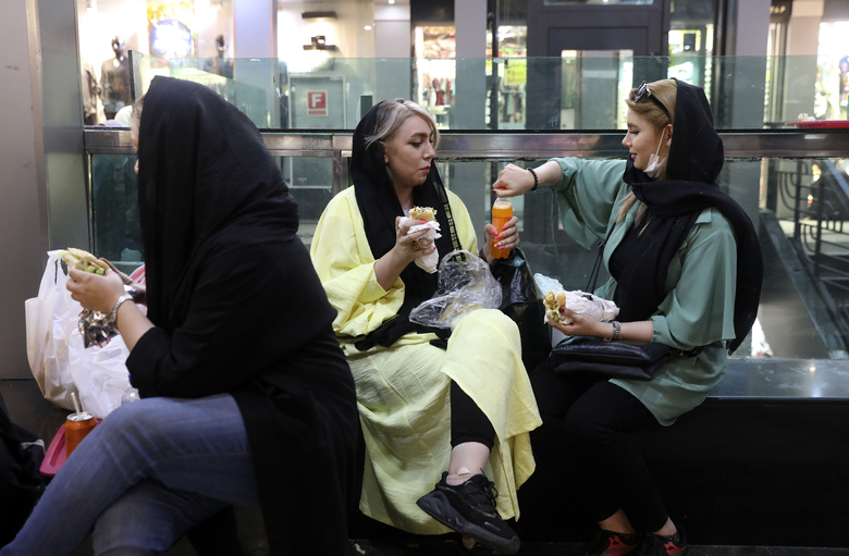 In this Wednesday, June 10, 2020, photo, people have their lunch in a shopping center at the Tehran's Grand Bazaar in Iran. As businesses open and people begin to move around more, health experts fear a growing complacency among Iran's 80 million people may further allow the virus to spread. (AP Photo/Vahid Salemi)
