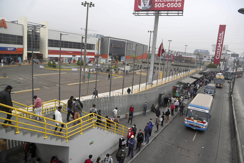 Hundreds of people wait in line outside of at Mega Plaza mall in Lima, Peru, Wednesday, June 24, 2020. Thousands of people crowded in hours-long lines after Peru's government ignored scientific warnings and opened the country's 90 shopping malls this week in the middle of one of the world's worst outbreaks of coronavirus. (AP Photo/Martin Mejia)