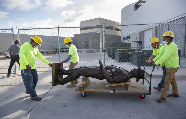 "A Phoenix 1 Restoration & Construction crew wheels a 12-foot-tall bronze statue of a Texas Ranger, called ""One Riot, One Ranger,""  from the main lobby inside Love Field airport on Thursday, June 4, 2020 in Dallas. A published account of brutal and racist chapters in the history of an elite Texas investigative agency prompted Dallas officials to remove the statue from Love Field's passenger terminal that honored the agency. (Juan Figueroa/ The Dallas Morning News via AP)"
