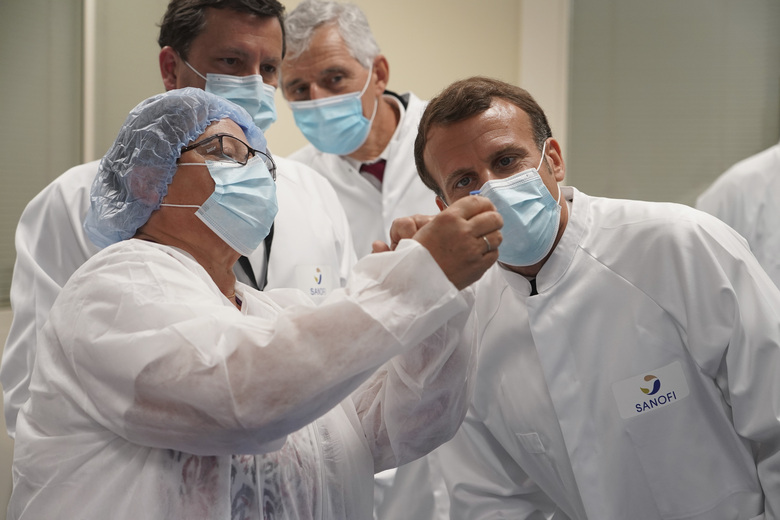 French President Emmanuel Macron visits an industrial development laboratory at French drugmaker's vaccine unit Sanofi Pasteur plant in Marcy-l'Etoile, near Lyon, central France, Tuesday, June 16, 2020.The visit comes after rival pharmaceutical company AstraZeneca this weekend announced a deal to supply 400 million vaccine doses to EU countries, including France. (AP Photo/Laurent Cipriani, Pool)
