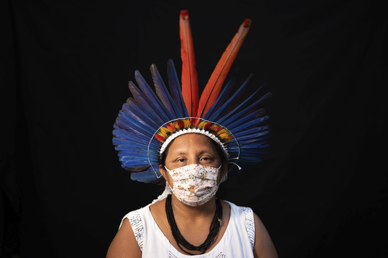 Sonia Vilacio, 46, of the Sateré Mawé indigenous ethnic group, poses for a portrait wearing the traditional dress of her tribe and a face mask amid the spread of the new coronavirus in Manaus, Brazil, Wednesday, May 27, 2020. The new coronavirus has hit Sônia Vilacio twice: when tourists disappeared from Manaus and she was left without an income from selling arts and crafts, and soon after when she fell ill with a fever, shortness of breath, and a cough, telltale signs of COVID-19. (AP Photo/Felipe Dana)