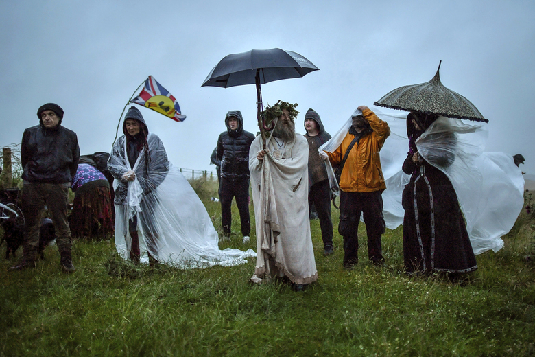 People gather as some shield from the rain next to the closed Stonehenge, to celebrate the Summer Solstice, the longest day of the year, near Salisbury, England, Sunday June 21, 2020. (Ben Birchall/PA via AP)