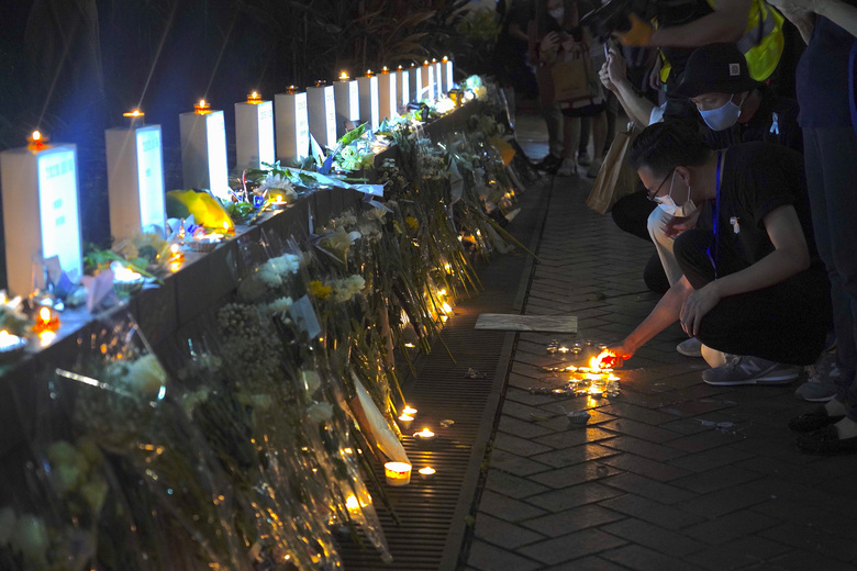 Mourners light candles as they pay respect at the site to mark one year memorial where a man fell to his death after hanging a protest banner against the extradition bill on the scaffolding of a shopping mall in Admiralty, Hong Kong, Monday, June 15, 2020. Protesters in Hong Kong got the government to withdraw extradition legislation last year, but now they're getting a more dreaded national security law, and the message from Beijing is that protest is futile. (AP Photo/Vincent Yu)