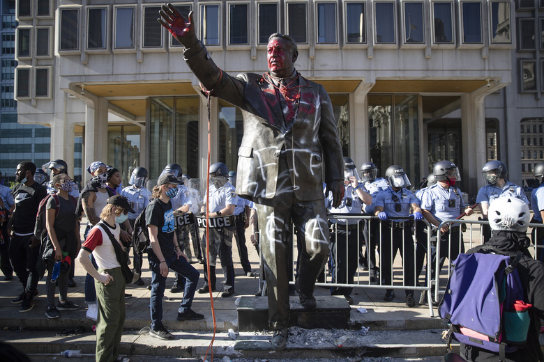In this Saturday, May 30, 2020 photo police stand near a vandalized statue of controversial former Philadelphia Mayor Frank Rizzo in Philadelphia, during protests over the death of George Floyd, who died May 25 after he was restrained by Minneapolis police. Workers early Wednesday, June 3 removed the statue which was recently defaced during the weekend protest. (AP Photo/Matt Rourke)