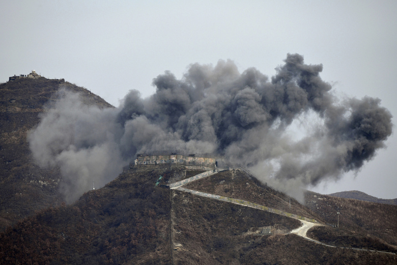 FILE – In this Nov. 15, 2018, file photo, smoke from an explosion rises as part of the dismantling of a South Korean guard post in the Demilitarized Zone dividing the two Koreas in Cheorwon, South Korea, as a North Korean guard post sits high in the upper left. On both sides of the world's most heavily armed border Thursday, June 25, 2020, solemn ceremonies will mark the 70th anniversary of the outbreak of a war that killed and injured millions, left large parts of the Korean Peninsula in rubble and technically still continues. (Jung Yeon-je/Pool Photo via AP, File)