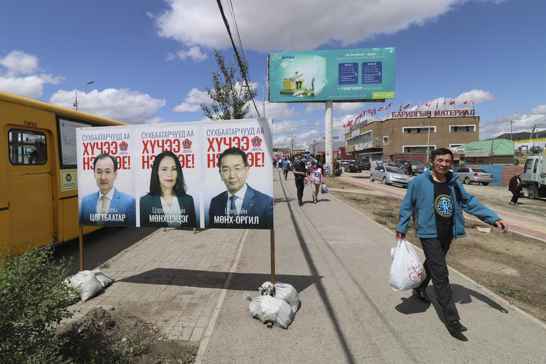 A man walks past an election poster of candidates of the ruling Mongolian People's Party (MPP) featuring current Foreign Minister Damdiny Tsogtbaatar, left, in the Chingeltei district, northern outskirts of Ulaanbaatar, Mongolia, Monday, June 22, 2020. Mongolia holds parliamentary elections on Wednesday, continuing a nearly 30-year democratic system in a vast but lightly populated country sandwiched between authoritarian regimes in Russia and China and beset by economic problems. (AP Photo/Ganbat Namjilsangarav)