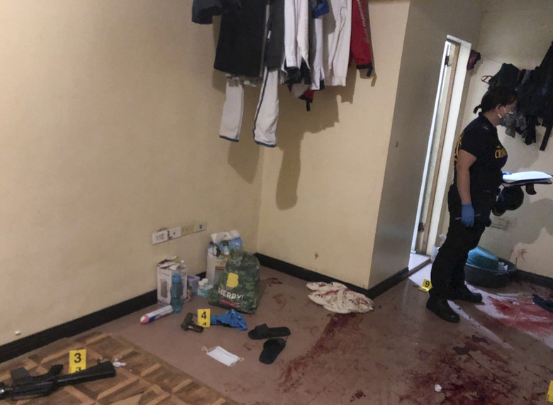 In this photo provided by the Philippine National Police (NCRPO), police inspect a hideout where four suspected Islamic State group-linked militants were killed during a gunbattle in metropolitan Manila, Philippines, Friday June 26, 2020. Police and intelligence agents were to serve a search a warrant at a house in a village in suburban Paranaque city after months of surveillance when the suspected militants opened fire, metropolitan Manila police chief Debold Sinas said. (Philippine National Police NCRPO via AP)