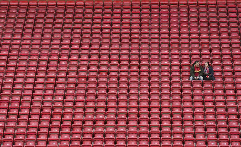 FILE – In this March 7, 2020, file photo, people sit surrounded by empty seats as they wait for the start of the English Premier League soccer match between Liverpool and Bournemouth at Anfield stadium in Liverpool, England. The crippling grip the coronavirus pandemic has had on the sports world has forced universities, leagues and franchises to evaluate how they might someday welcome back fans. (AP Photo/Jon Super, File)